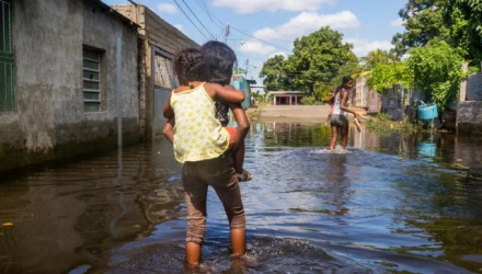 A family wades through a flooded street in San Felix, Bolivar State, Venezuela, on August 10, 2018. The Orinoco river floods have damage houses, crops and generate a potential outbreak to diseases for which medicines are lacking. The floods affect eight states, according to the government. / AFP PHOTO / William R. Urdaneta