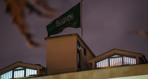 "A Turkish forensic stands next to the Saudi flag, on the roof of the Saudi Arabia's consulate in Istanbul on October 15, 2018 during the investigation over missing Saudi journalist Jamal Khashoggi. - Turkish police searched the Saudi consulate in Istanbul for the first time since journalist Jamal Khashoggi went missing, as US President floated the idea that ""rogue killers"" could be to blame for his disappearance. (Photo by OZAN KOSE / AFP)"