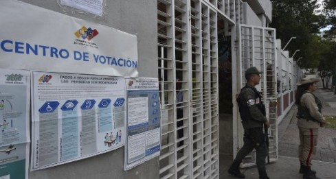 A member of the Bolivarian National Guard (L) stands at the main door of a polling station in Caracas during Venezuela's municipal council elections, on December 9, 2018. - The election, in which opposition parties were banned from participating, comes one month before President Nicolas Maduro begins his second term (2019-2025) in office after winning an election in May considered illegitimate by the political opposition and unrecognised by the European Union, the United States and most of Latin America. (Photo by YURI CORTEZ / AFP)